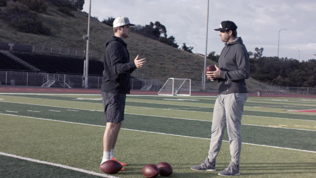 In this April 19, 2018, photo provided by Wilson Sporting Goods, quarterback Sam Darnold, left, speaks with his mentor and former NFL quarterback Jordan Palmer about using the Wilson Connected Football System, at San Clemente High School in San Clemente, Calif. Wilson is hoping to have the 2.0 version of its Connected Football technology available for a more open release to college and pro teams later this year. In the meantime, the company is gathering feedback from players and coaches at both levels. (Wilson Sporting Goods via AP)