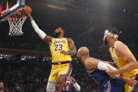 Los Angeles Lakers forward LeBron James (23) goes up for two points as New York Knicks forward Taj Gibson (67) is restrained by a Lakers defender, right, during the first half of an NBA basketball game in New York, Wednesday, Jan. 22, 2020. (AP Photo/Kathy Willens)