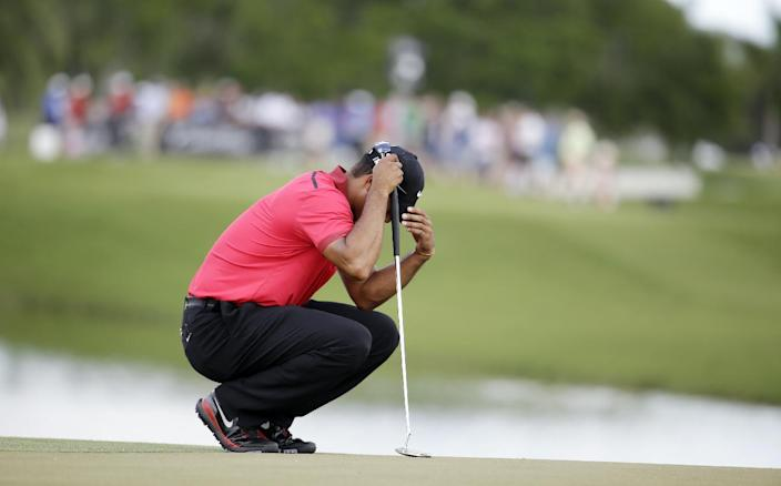 Tiger Woods bows his head on the fourth green during the final round of the Cadillac Championship golf tournament on Sunday, March 9, 2014, in Doral, Fla. Woods made bogey on the hole. (AP Photo/Lynne Sladky)