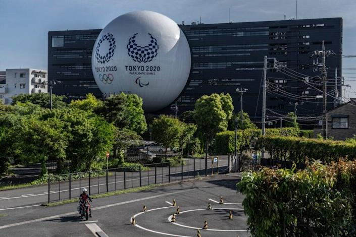 A huge semi-sphere displaying the Tokyo Olympics and Paralympics logos is displayed from the side of a driving school building on May 6, 2021 in Tokyo, Japan. (Photo by Carl Court/Getty Images)