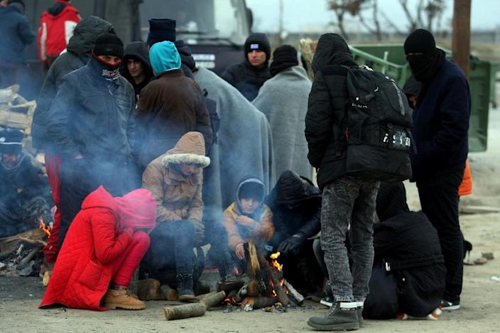 Migrants and refugees warm themselves by a fire as they wait to cross the Greek-Macedonian border, near Idomeni on January 20, 2016 (AFP Photo/Sakis Mitrolidis)