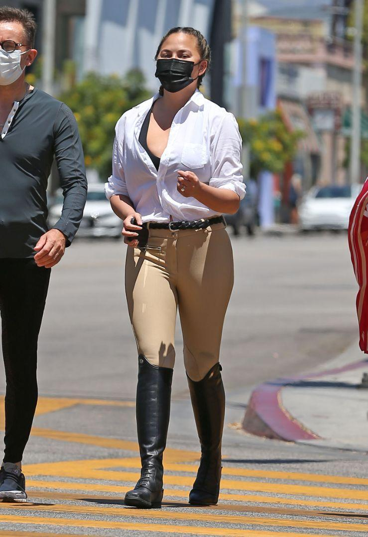 Chrissy Teigen is seen wearing riding pants and boots while out shopping on Melrose in Los Angeles, July 20. - Credit: carlosmaidanaphotography/MEGA