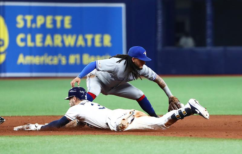 Aug 6, 2019; St. Petersburg, FL, USA; Tampa Bay Rays center fielder Kevin Kiermaier (39) doubles against Toronto Blue Jays shortstop Freddy Galvis (16) during the tenth inning at Tropicana Field. Mandatory Credit: Kim Klement-USA TODAY Sports