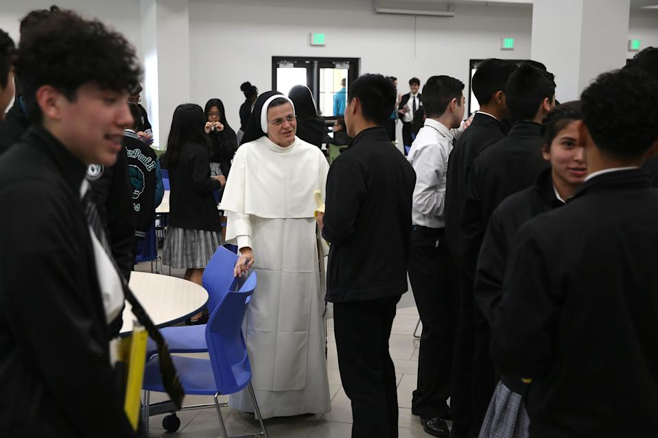 Sister Mary Jordan Hoover, the principal of the St. John Paul II Catholic School, talks with students during lunch break in Phoenix, Ariz., on Feb. 26, 2020. In the western suburbs of Phoenix, enrollment is surging at this new Catholic high school built to serve a fast-growing, heavily Hispanic community. (AP Photo/Dario Lopez-MIlls)
