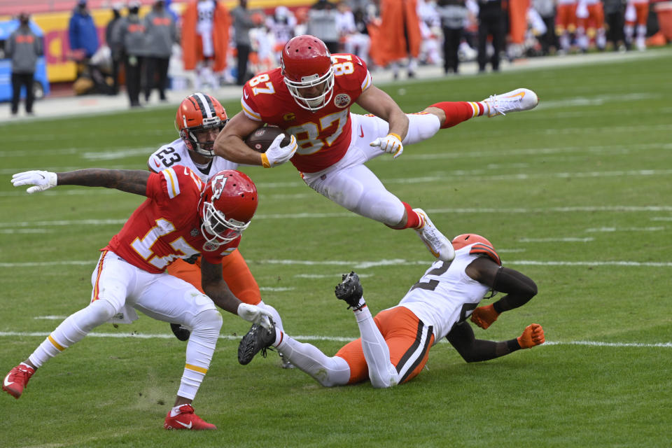 Kansas City Chiefs tight end Travis Kelce (87) leaps over Cleveland Browns safety Karl Joseph, right, during a 20-yard touchdown reception in the first half of an NFL divisional round football game, Sunday, Jan. 17, 2021, in Kansas City. (AP Photo/Reed Hoffmann)
