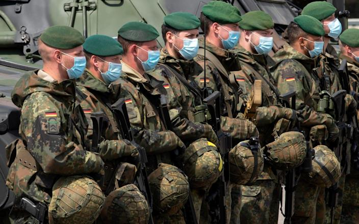 Soldiers of the German Federal Armed Forces Bundeswehr wear face maks as they attend a press presentation showing the battlefield management system (BMS) in the 37th armoured infantry regiment in Frankenberg, eastern Germany, Tuesday, May 26, 2020. A battlefield management system (BMS) is a digital system meant to integrate information acquisition and processing to enhance command and control of a military unit. The Battle Management System (BMS) has been introduced in the German armed forces base since early April 2020 and also in the Bundeswehr army since May 11, 2020. (AP Photo/Jens Meyer) - Jens Meyer/AP