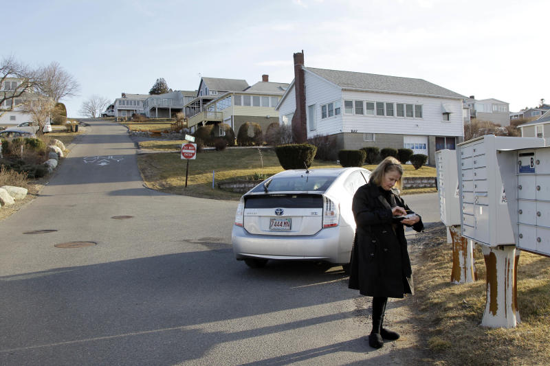 In this photo of Wednesday, Feb. 22, 2012, resident Linda Saunders pauses by her mailbox on Little Neck in Ipswich, Mass. The dying wish of William Payne, one of the state's earliest settlers, created the nation's oldest charitable trust and eventually led tenants to build 167 cottages on this land he left for the seaside city. The rent money has generated some $2.4 million to help fund public schools over the last 25 years. Now, the trustees want to tear up the will and convert the property into condominiums. (AP Photo/Elise Amendola)