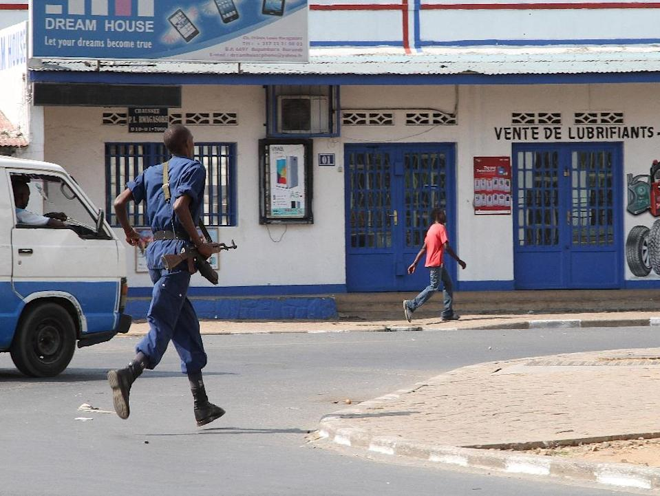 A lone police officer runs in the direction of the old market in the Burundian capital, Bujumbura August 2 2015. A top Burundian general and close aide to President Pierre Nkurunziza was killed in an ambush on his car in the capital Bujumbura, officials and witnesses said. The general killed, Adolphe Nshimirimana, was widely seen as the crisis-hit central African nation's de facto internal security chief and even considered the regime's number-two . AFP PHOTO/Landry NSHIMIYE (AFP Photo/Landry Nshimiye)