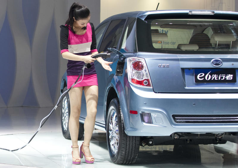 A woman demonstrates BYD's new charging and discharging technology on a BYD e6 electric car during the 2012 Beijing International Automotive Exhibition in Beijing, China, Monday, April 23, 2012. (AP Photo/Alexander F. Yuan)