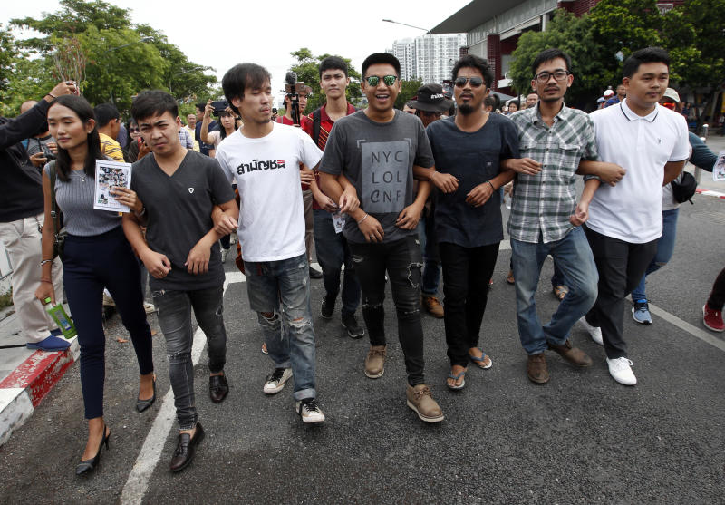 Activist Jatupat Boonpattararaksa, fourth from left, gathers with another political activist outside Pathumwan police station in Bangkok, Thailand, Wednesday, May 22, 2019. Thirteen Thai political activists have appeared at a Bangkok police station to answer a summons on sedition charges that critics say are part of a plan to remove a rising progressive politician from the political scene. (AP Photo/Sakchai Lalit)