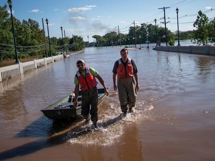 United States Geological Survey workers push a boat as they look for residents on a street flooded as a result of the remnants of Hurricane Ida in Somerville, NJ., Thursday, Sept. 2, 2021.