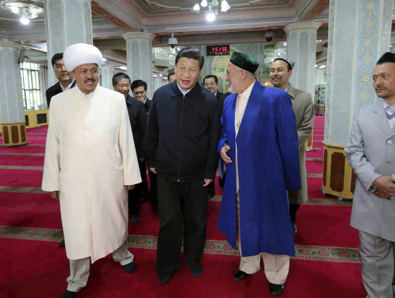 In this Wednesday, April 30, 2014 photo released by China's Xinhua News Agency, Chinese President Xi Jinping, front center, visits a mosque in Urumqi, capital of northwest China's Xinjiang Uygur Autonomous Region. Xi had an inspection tour in Xinjiang from April 27 to April 30. (AP Photo/Xinhua, Lan Hongguang) NO SALES