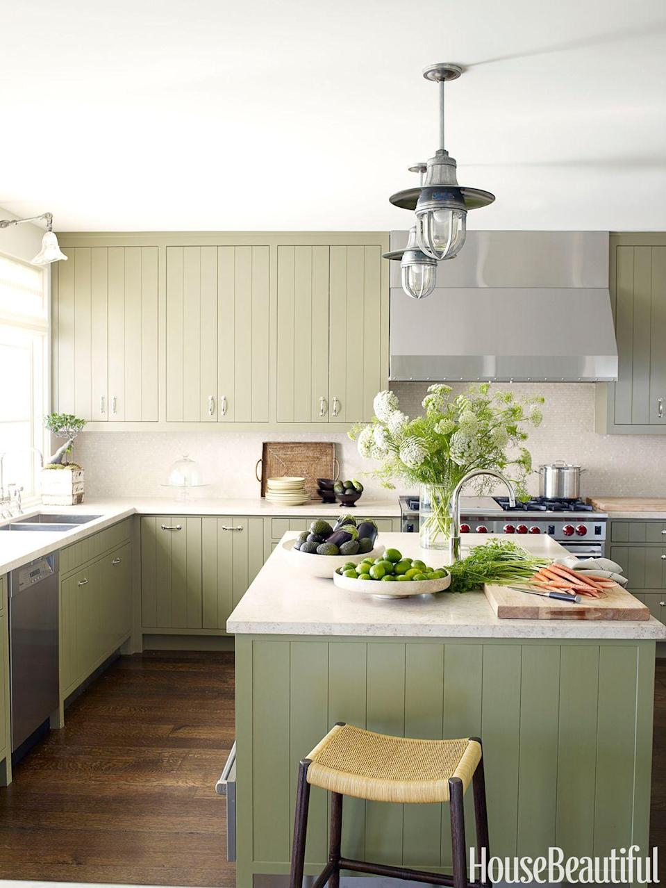 "<p>Create a modern Provincial kitchen with minimalist grooved cabinetry in a <a href=""https://www.housebeautiful.com/room-decorating/colors/a14516597/sage-trend-2018/"" rel=""nofollow noopener"" target=""_blank"" data-ylk=""slk:soft custom sage green"" class=""link rapid-noclick-resp"">soft custom sage green</a> and limestone countertops. The kitchen feels simultaneously masculine and warm & inviting. </p>"