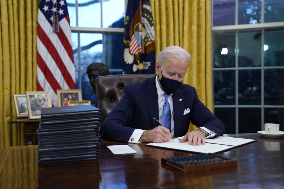 President Joe Biden signs his first executive order in the Oval Office of the White House on Wednesday, Jan. 20, 2021, in Washington. (Evan Vucci/AP)