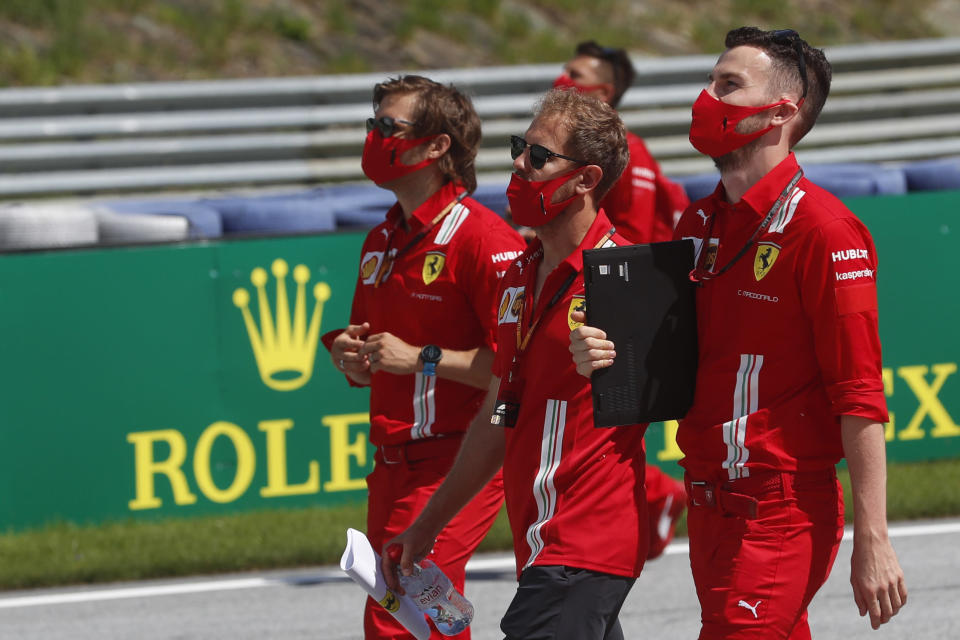 Ferrari driver Sebastian Vettel, center, inspects the track with his team at the Red Bull Ring racetrack in Spielberg, Austria, Thursday, July 2, 2020. Austrian Formula One Grand Prix will be held on Sunday. (AP Photo/Darko Bandic)