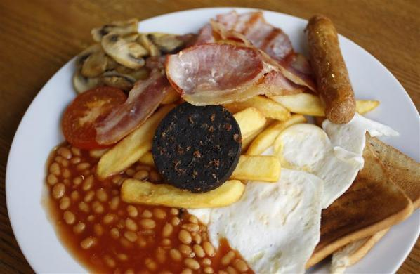 A traditional full English breakfast of sausages, chips, baked beans, bacon, black pudding and toast. Photographed at 'Enough To Feed an Elephant' cafe in London.