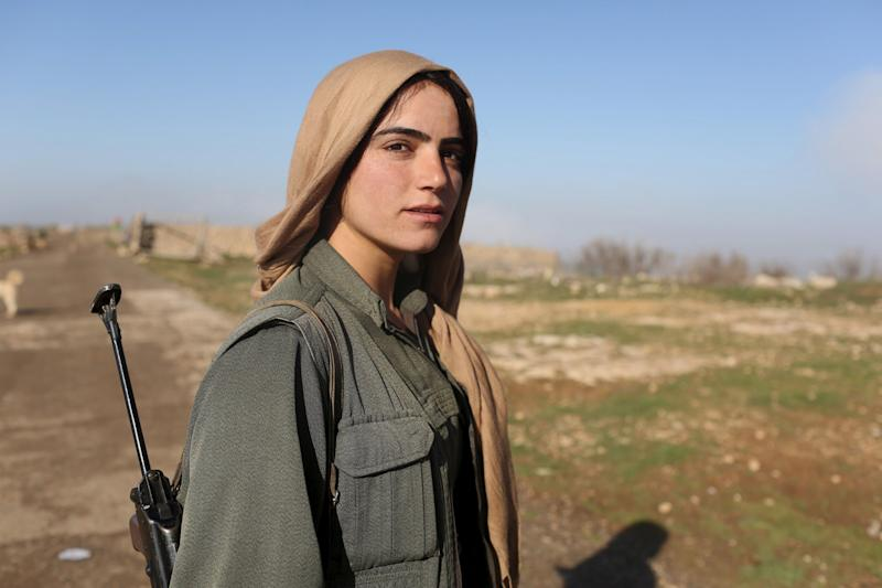 A female Kurdistan Workers Party (PKK) fighter stands near a security position in Sinjar, March 13, 2015. Women fighters at a PKK base on Mount Sinjar in northwest Iraq, just like their male counterparts, have to be ready for action at any time. Smoke from the front line, marking their battle against Islamic State, which launched an assault on northern Iraq last summer, is visible from the base. Many of the women have cut links with their families back home; the fighters come from all corners of the Kurdish region.
