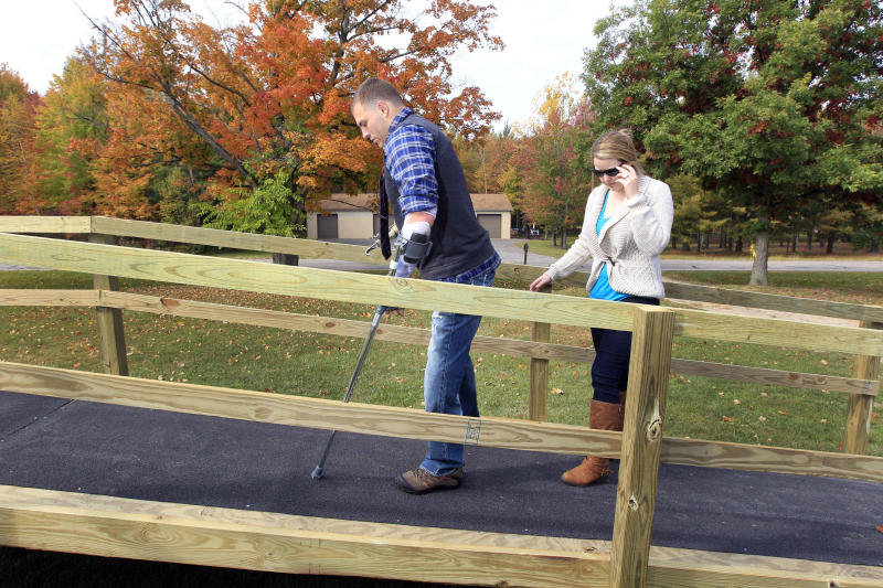 Kelsey Mills helps her husband, Army Staff Sgt. Travis Mills, navigate the newly installed ramp at his boyhood home in Vassar, Mich., Thursday, Oct. 4, 2012. Mills is visiting his hometown for the first time since losing all four limbs while fighting in Afghanistan. Mills, his wife, Kelsey, and their 1-year-old daughter, Chloe, will be the grand marshals of Vassar High School's homecoming parade on Thursday evening. (AP Photo/Carlos Osorio)