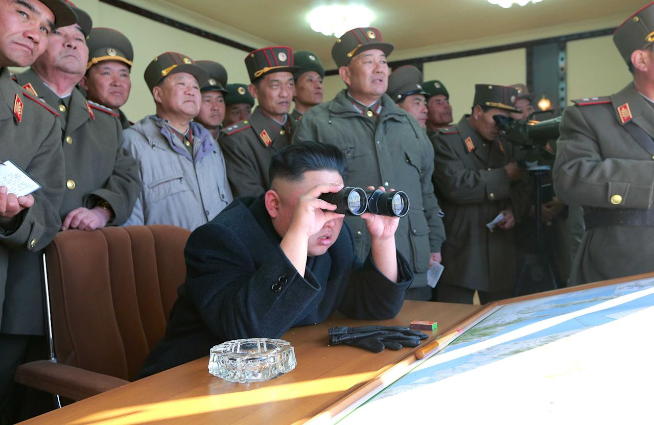 In this undated photo released by the Korean Central News Agency (KCNA) and distributed Thursday, March 14, 2013 by the Korea News Service, North Korean leader Kim Jong Un uses a pair of binoculars to watch live ammunition firing drills by the Jangjae Islet Defense Detachment and the Mu Islet Hero Defense Detachment deployed in the southwestern sector in North Korea. (AP Photo/KCNA via KNS) JAPAN OUT UNTIL 14 DAYS AFTER THE DAY OF TRANSMISSION