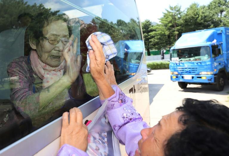 South Koreans (on the bus) wave farewell through the window to their North Korean relatives at the end of the reunion