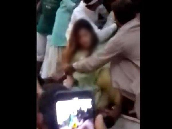A visual of a mob of men attacking a woman in Pakistan (Photo credit: Twitter@qiranbutt)