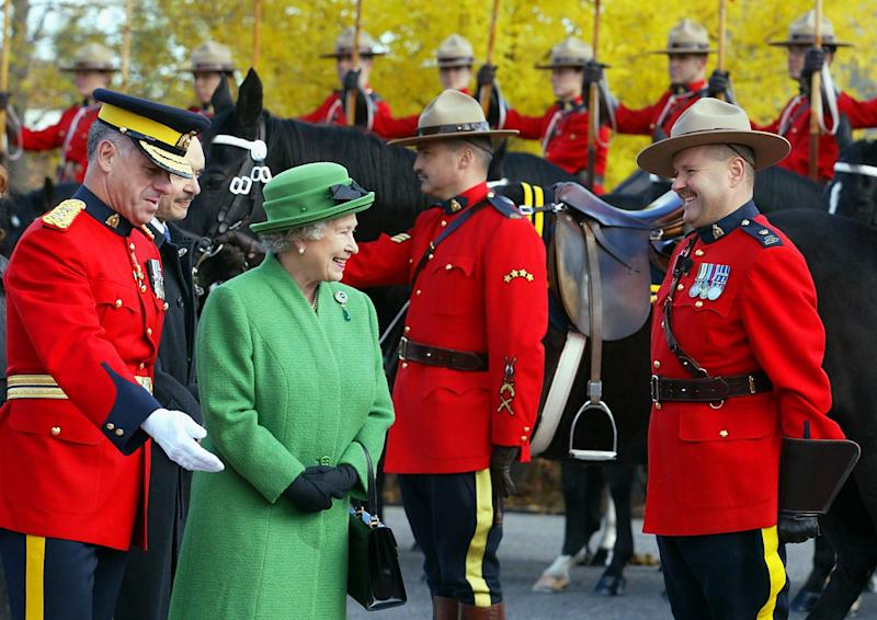 OTTAWA, CANADA: Britain's Queen Elizabeth II is greeted by members of the Royal Canadian Mounted Police musical ride at their headquarters with RCMP commissioner Giuliano Zaccardelli (L) in Ottawa,14 October 2002. Her majesty the Queen and the Duke of Edinburgh are on a two-week tour of Canand. AFP PHOTO/Tom Hanson (Photo credit should read TOM HANSON/AFP via Getty Images)