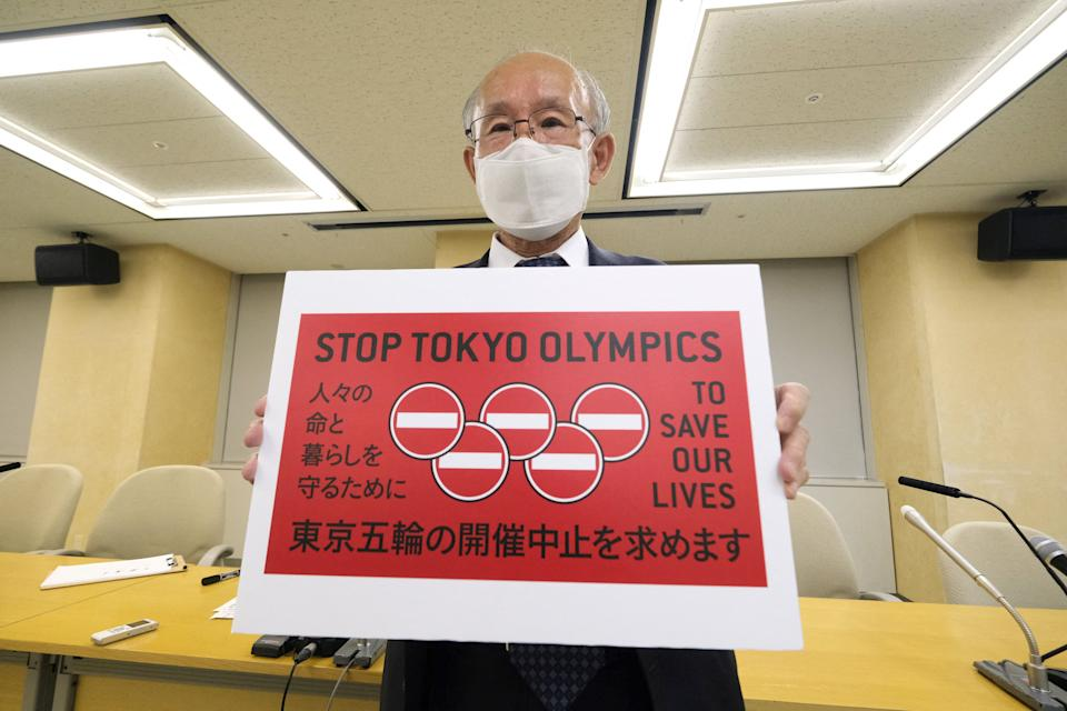 Kenji Utsunomiya, a Japanese lawyer and former Tokyo gubernatorial candidate, poses with a campaign slogan Stop Tokyo Olympics.