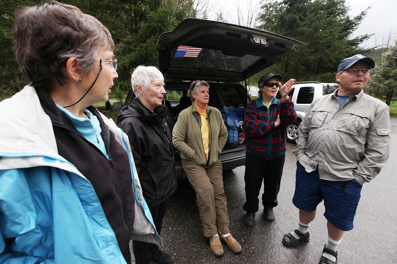 A group of hikers talks about their proposed hike at a trailhead several miles from where a gun-toting survivalist is suspected of killing his wife and daughter several days earlier Friday, April 27, 2012, in North Bend, Wash. From left are Jane Falding, Sally Betts, Dixie Green and Judy and Roy Hines. Peter Alex Keller may be holed up in a self-made fort not far from where Seattle's outer suburbs give way to the vast recreational playground of Cascade Mountains. Police expect more people to hit the nearby trails this weekend, and deputies are warning them to steer clear of Keller if they think they see him. (AP Photo/Elaine Thompson)