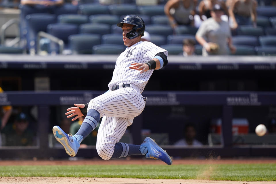New York Yankees' Aaron Judge heads home while trying to beat the throw to the plate on Gary Sanchez's two-run double during the sixth inning of a baseball game against the Oakland Athletics, Sunday, June 20, 2021, at Yankee Stadium in New York. (AP Photo/Kathy Willens)