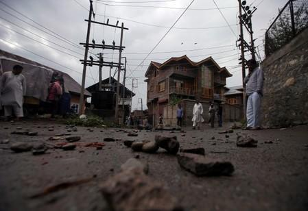 People walk on a road covered with stones and pieces of bricks, in Srinagar