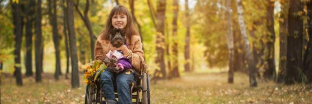 Woman in a wheelchair holding a small dog in autumn landscape.