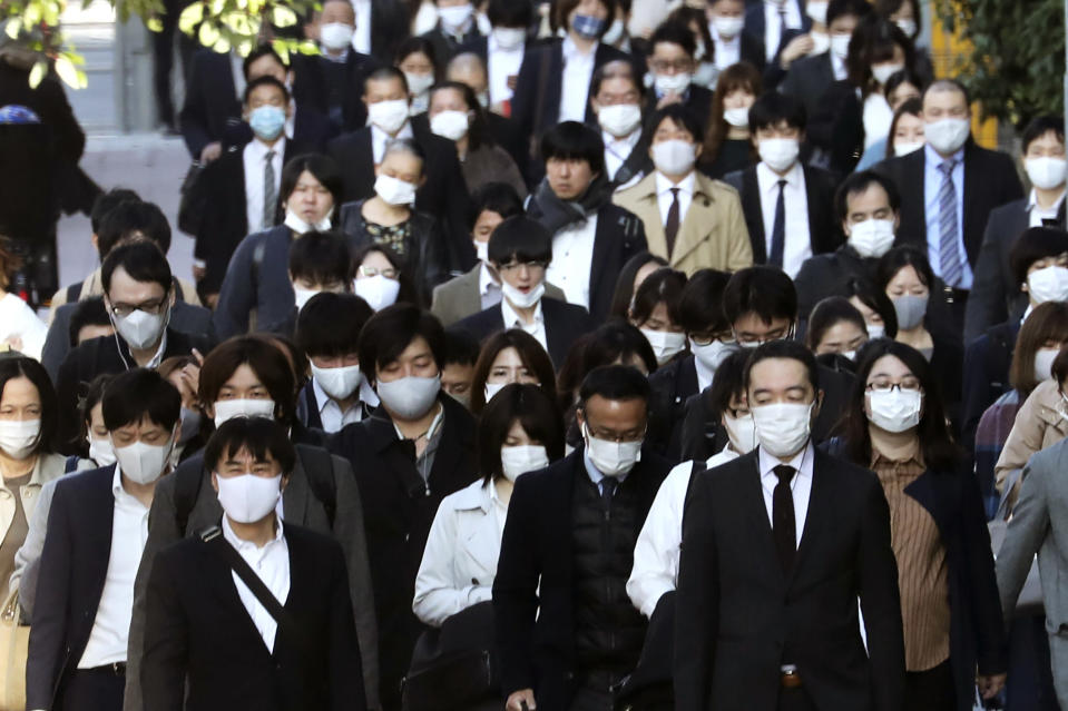 Commuters wearing face masks to protect against the spread of the coronavirus walk on a street in Tokyo, Tuesday, Nov. 17, 2020. (AP Photo/Koji Sasahara)
