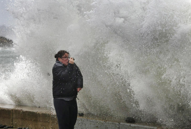 Lisa Famularo braces for impact as a large wave crashes over a seawall while she photographed heavy surf in the Atlantic Ocean during the early stages of Hurricane Sandy, Monday, Oct. 29, 2012, in Kennebunk, Maine. Hurricane Sandy continued on its path Monday, as the storm forced the shutdown of mass transit, schools and financial markets, sending coastal residents fleeing, and threatening a dangerous mix of high winds and soaking rain.(AP Photo/Robert F. Bukaty)