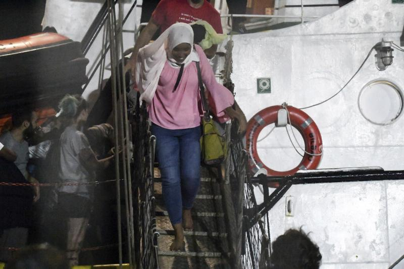 In this photo taken on Tuesday, Aug. 20, 2019, a woman disembarks from the Open Arms rescue ship on the Sicilian island of Lampedusa, southern Italy. An Italian prosecutor ordered the seizure of a rescue ship and the immediate evacuation of more than 80 migrants still aboard, capping a drama Tuesday that saw 15 people jump overboard in a desperate bid to escape deteriorating conditions on the vessel and Spain dispatch a naval ship to try to resolve the crisis. (AP Photo/Salvatore Cavalli)
