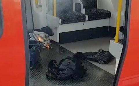 Personal belonglongs and a bucket with an item on fire inside it, are seen on the floor of an underground train carriage at Parsons Green station - Credit: SYLVAIN PENNEC/REUTERS