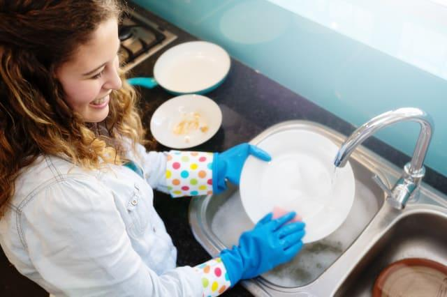 Cute, curly-haired girl does the dishes, smiling
