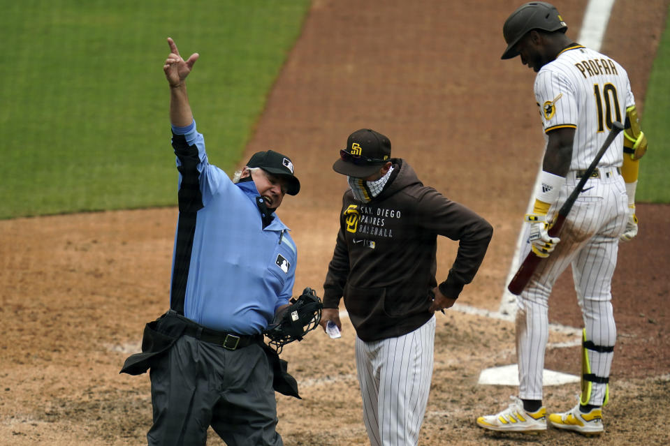 Umpire Tom Hallion, left, ejects San Diego Padres manager Jayce Tingler, center, as San Diego Padres' Jurickson Profar waits to bat during the eighth inning of a baseball game against the Milwaukee Brewers Wednesday, April 21, 2021, in San Diego. (AP Photo/Gregory Bull)