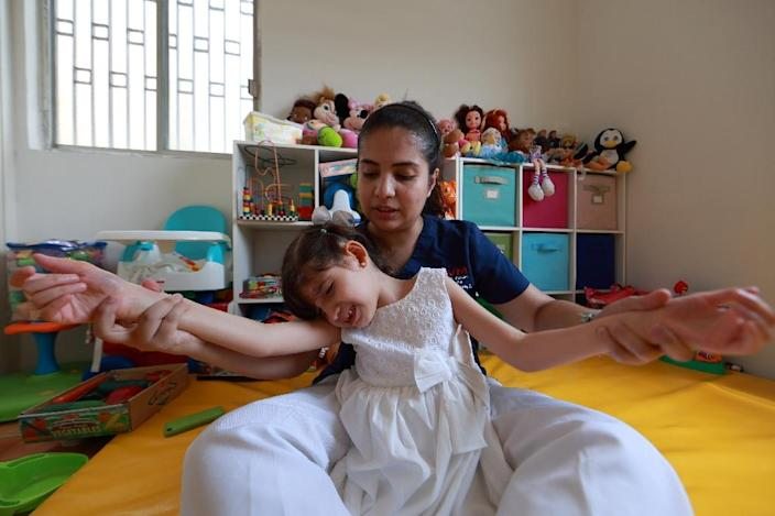 Physiotherapist Ana Campos visits Graciela Elizalde at her home in the Guadalupe municipality near Monterrey (AFP Photo/Carlos Ramirez)