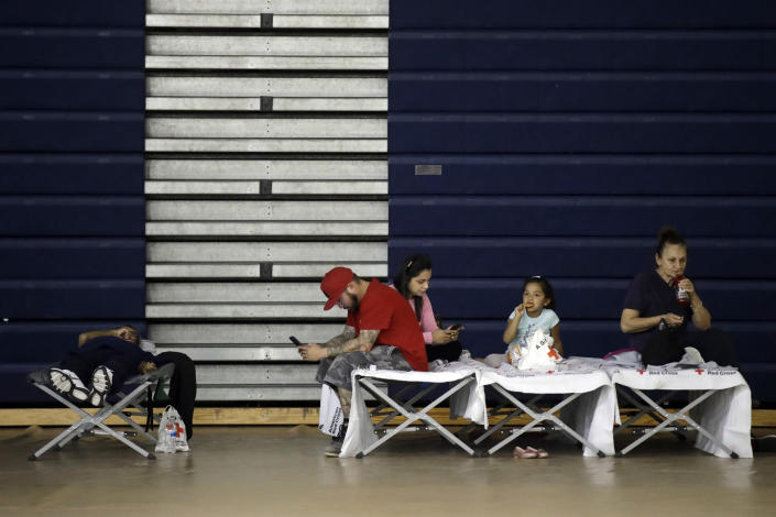 Evacuees from the Tick Fire sit on cots inside the gym at West Ranch High School Friday, Oct. 25, 2019, in Santa Clarita, Calif. (AP Photo/Marcio Jose Sanchez)