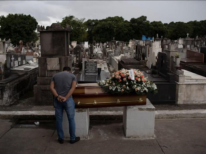 A man mourns next to the coffin containing the remains of a relative who died from complications related to COVID-19 at the Inahuma cemetery in Rio de Janeiro, Brazil (AP)