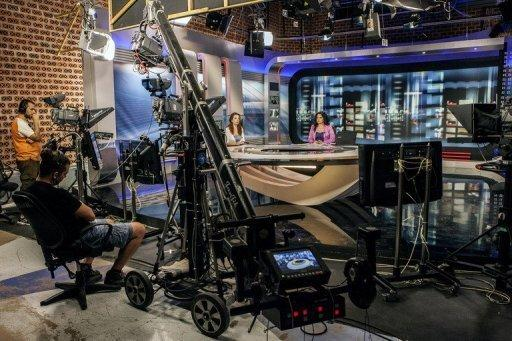 ERT journalists and technicians broadcast a news report at the ERT headquarters in Athens, on July 10, 2013. Greek lawmakers have narrowly approved a bill outlining a new public TV and radio network, more than a month after the government's shutdown of state broadcaster ERT.