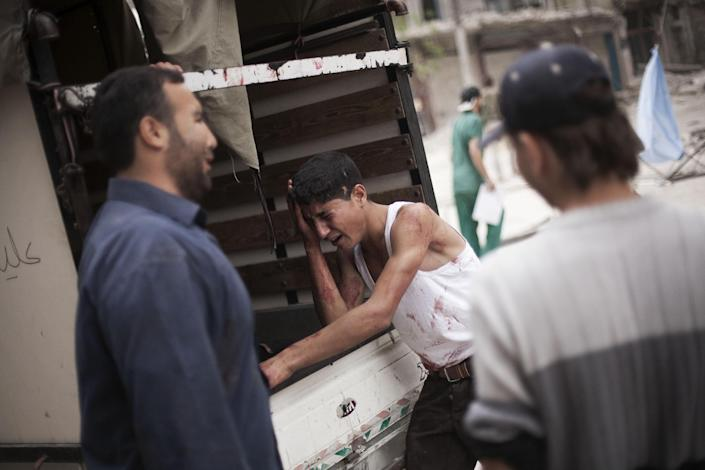 In this Thursday, Oct. 11, 2012 photo, a Syrian youth cries next to the truck holding the body his brother, killed by Syrian Army shelling, outside Dar al-Shifa hospital in Aleppo, Syria. (AP Photo/ Manu Brabo)