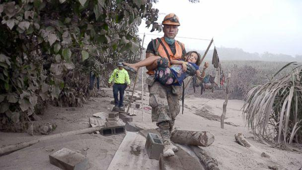PHOTO: A Guatemalan rescue team worker carries a girl in El Rodeo, Escuintla, Guatemala, June 3, 2018, after the eruption at Fuego volcano, which has left at least 25 dead, around 20 injured and more than 1.7 million people were affected. (Noe Perez/EPA via Shutterstock)