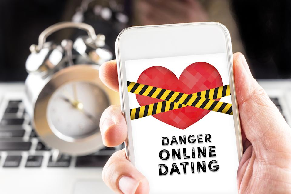 Hand holding mobile with caution tape on heart and Danger online dating  on screen with clock and laptop at background.