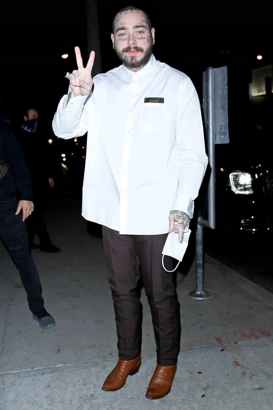 <p>Post Malone throws up a peace sign outside of BOA Steakhouse on Friday in West Hollywood.</p>