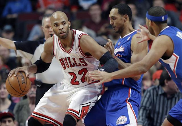 Chicago Bulls forward Taj Gibson (22), left, drives as he looks to a pass against Los Angeles Clippers center Ryan Hollins, center, and forward Jared Dudley during the first half of an NBA basketball game in Chicago on Friday, Jan. 24, 2014. (AP Photo/Nam Y. Huh)