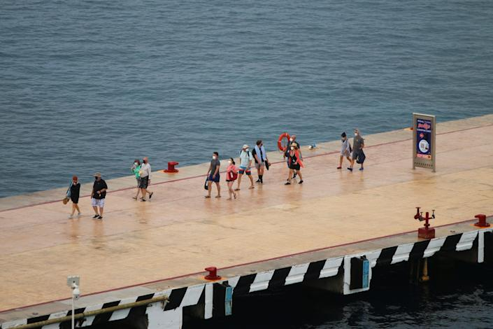This image shows about 10 people standing in a loose line on a strip overlooking the ocean.