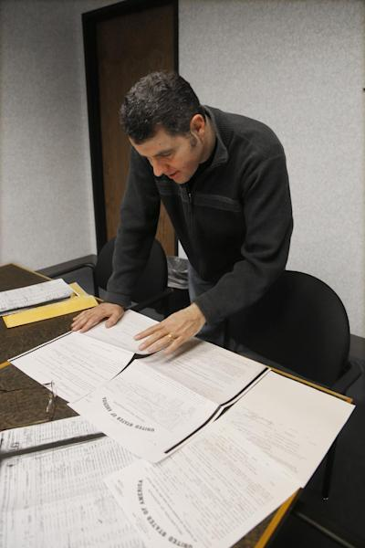 In this Dec. 18, 2012 photo, Detroit Associated Press reporter Jeff Karoub looks over immigration papers of his grandfather Hussien Karoub in Detroit. Wanting to fill some ancestral gaps, Jeff is piecing together the story of his grandfather who immigrated to America in 1912. (AP Photo/Carlos Osorio)