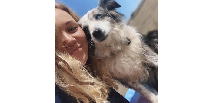 This undated selfie photo provided by Emilie Talermo showing Emilie Talermo and her dog Jackson taken in San Francisco, Calif. Talermo, is offering a $7,000 reward for her blue-eyed miniature Australian Shepherd stolen from outside a grocery store. She has hired a plane to fly a banner over the city. Talermo said Thursday, Dec. 19, 2019, she has been doing everything she can to find her dog, since it was stolen Saturday, Dec. 14, 2019, outside a grocery store in the Bernal Heights neighborhood. (Emilie Talermo via AP)