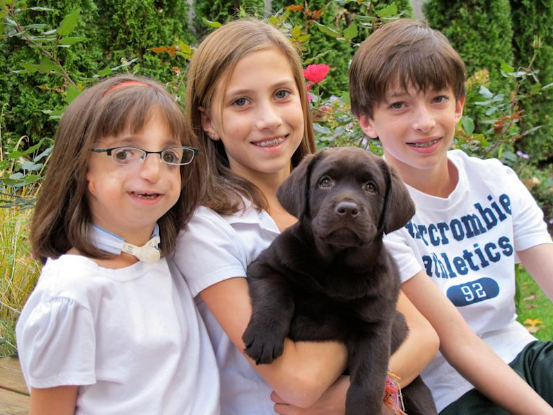 In this Oct. 24, 2010 photo provided by the family, Clara Beatty, then 8, poses with the family dog with sister Gretchen and brother Henry at their Winnetka, Ill. home. Unlike her siblings, Clara was born with facial deformities cased by a genetic mutation called Treacher Collins syndrome. (AP Photo)